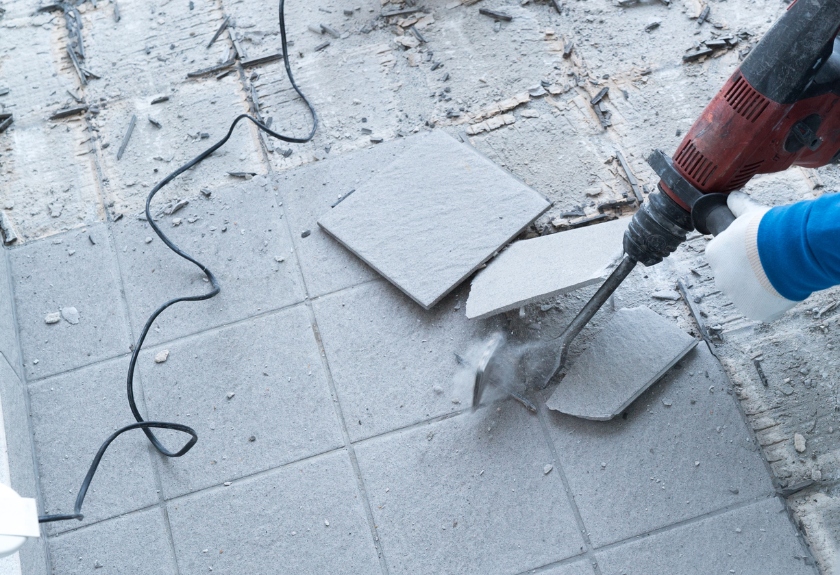 construction worker using a handheld demolition hammer and wall